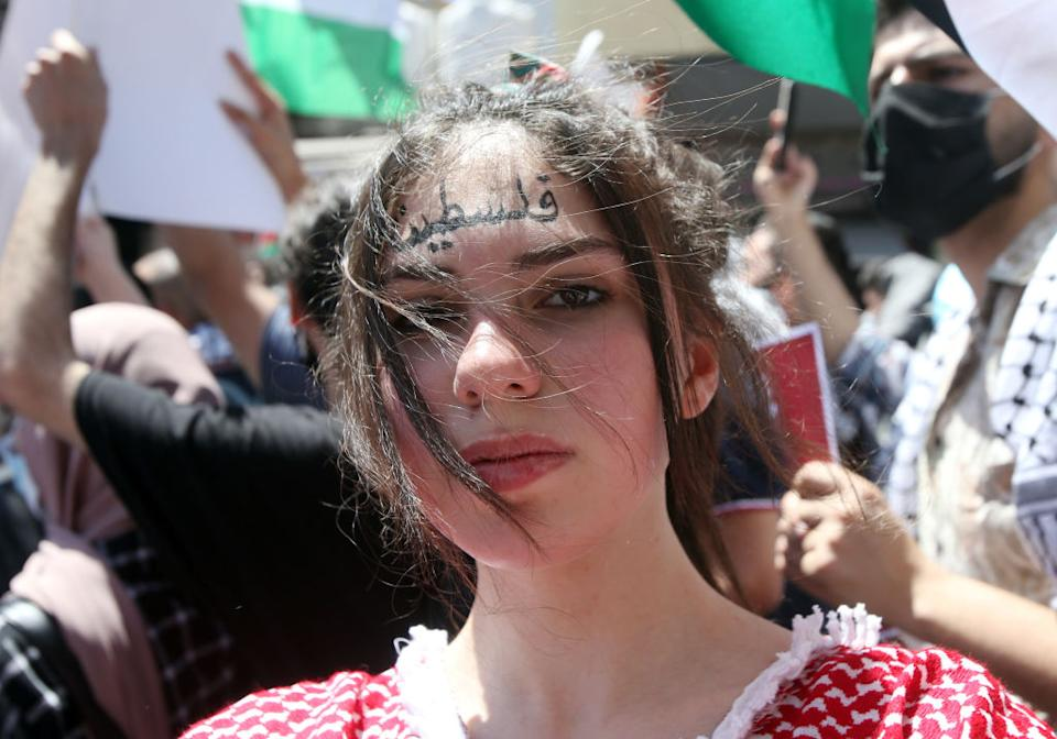 A young girl with 'Palestine' in Arabic letters written on her face is seen as Jordanians march in the downtown centre protesting in solidarity with Gazans during the current conflict with Israel, in Amman, Jordan.