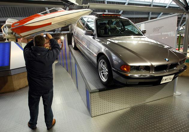 "A man photographs the Glastron GT-150 Jump Boat from the 1973 Bond film ""Live and Let Die"" with the BMW 750iL from the 1997 film ""Tomorrow Never Dies"" at the opening of a press preview of the Bond in Motion exhibition at the Beaulieu National Motor Museum at Brockenhurst in the southern English county of Hampshire on January 15, 2012. The Bond in Motion exhbition features fifty original iconic vehicles used in the James Bond films to celebrate fifty years of 007 and will open to the public from January 17. AFP PHOTO / JUSTIN TALLIS"