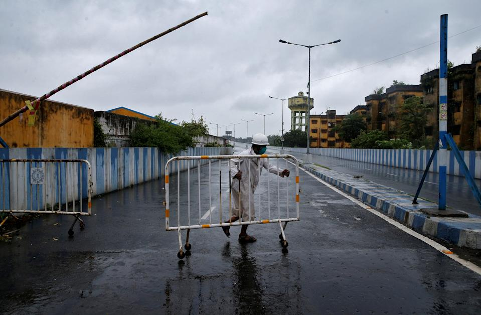 A police officer moves a barricade to block a road leading to a flyover before Cyclone Amphan makes its landfall, in Kolkata, India, May 20, 2020. REUTERS/Rupak De Chowdhuri
