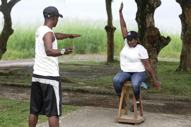 Paralympic athlete Audray Fabiola Mengue Pambo uses a wooden stool to warm up for the shot put