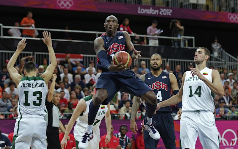 USA's Kobe Bryant drives to the basket between Lithuania's Sarunas Jasikevicius, left and Jonas Valanciunas during a men's basketball game at the 2012 Summer Olympics, Saturday, Aug. 4, 2012, in London. (AP Photo/Charles Krupa)