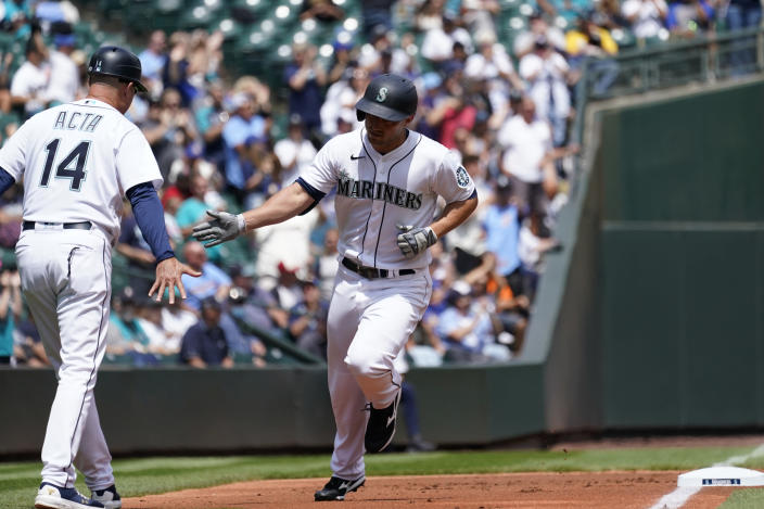 Seattle Mariners' Kyle Seager, right, is congratulated by third base coach Manny Acta as Seager rounds the bases on his solo home run against the New York Yankees in the first inning of a baseball game Thursday, July 8, 2021, in Seattle. (AP Photo/Elaine Thompson)