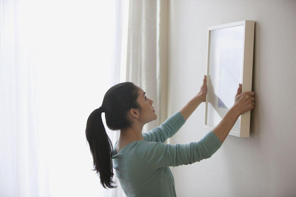 """<p>Almost all interior designers noted that most people out there hang their artwork or picture frames way too high, an issue you won't really notice until you fix it. """"The rule of thumb should be that your eye height is about aligned with the top third of the piece you are hanging,"""" says Cutler. </p><p>Interior designer, design coach, and author <a href=""""http://www.pamela-durkin.com/"""" rel=""""nofollow noopener"""" target=""""_blank"""" data-ylk=""""slk:Pamela Durkin"""" class=""""link rapid-noclick-resp"""">Pamela Durkin</a>, ASID, LEED AP ID+C, goes into it in a little more detail saying, """" I like art to be visually connected to a piece of furniture or fill up a wall space. If placing art above a sofa, I like it to start about 8-10"""" above the back so that it is close enough to feel like it is part of the scheme but far enough so you won't bump it when sitting on the sofa. I like to hang bigger pieces on a wall in the middle, so there is an even amount of space from top to bottom. Smaller pieces need to be grouped closer together (so they read as one element), about 2"""" apart and I like the middle of the piece to be at about 5-5""""-6"""" off the floor."""" Keep these rules in mind when hanging new pieces. <br></p>"""