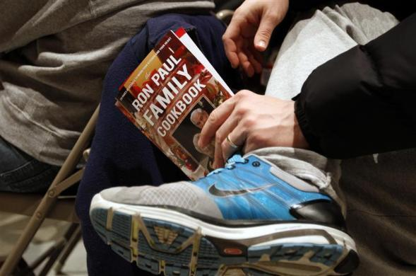"Don Harvey holds the ""Ron Paul Family Cookbook"" while listening to Ron Paul speak during a town hall meeting during a campaign stop in Marshalltown, Iowa December 10, 2011. (REUTERS/Jeff Haynes)"