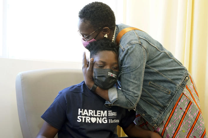 Julian Boyce, 14, gets a hug from his mother, Satrina Boyce, after he received his first Pfizer COVID-19 vaccination dose at NYC Health + Hospitals/Harlem, in New York, Thursday, May 13, 2021. New York Gov. Andrew Cuomo announced Wednesday that children between the ages of 12 and 15 can get vaccinated in New York effective immediately. (AP Photo/Richard Drew)