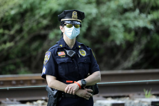 A police officer wears a face mask to protect agains the new coronavirus while looking at the 13th tee box during the final round of the Travelers Championship golf tournament at TPC River Highlands, Sunday, June 28, 2020, in Cromwell, Conn. (AP Photo/Frank Franklin II)