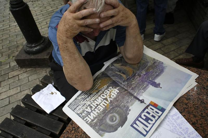 A man reads a newspaper with the front page depicting the plane crash of Malaysia Airlines flight MH17 in Kiev on July 18, 2014 (AFP Photo/Anatolii Stepanov)