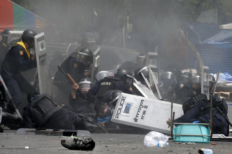 Thai police officers react after an explosion during clashes with anti-government protesters near Government House in Bangkok February 18, 2014. At least three police officers were wounded as Thai authorities launched an operation to clear anti-government protesters from streets in Bangkok on Tuesday. REUTERS/Athit Perawongmetha (THAILAND - Tags: POLITICS CIVIL UNREST)