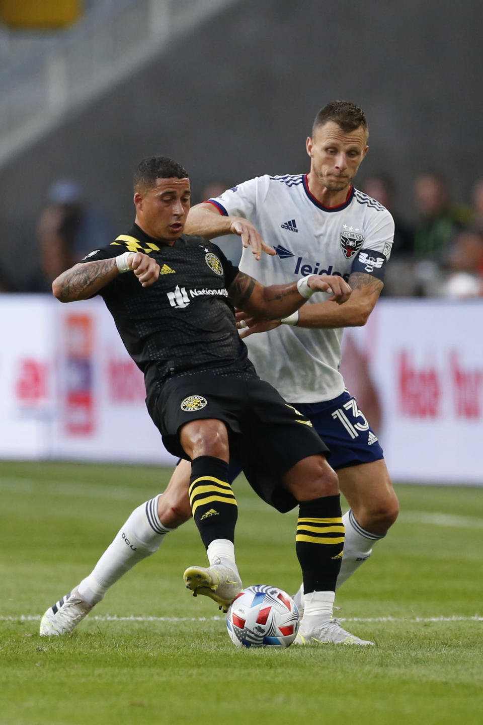 Columbus Crew's Erik Hurtado, left, and D.C. United's Frederic Brillant vie for the ball during the first half of an MLS soccer match Wednesday, Aug. 4, 2021, in Columbus, Ohio. (AP Photo/Jay LaPrete)