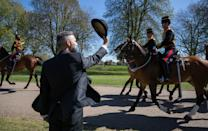 <p>A person salutes the King's Troop Royal Horse Artillery as they make their way down the Long Walk towards Windsor Castle. (PA)</p>