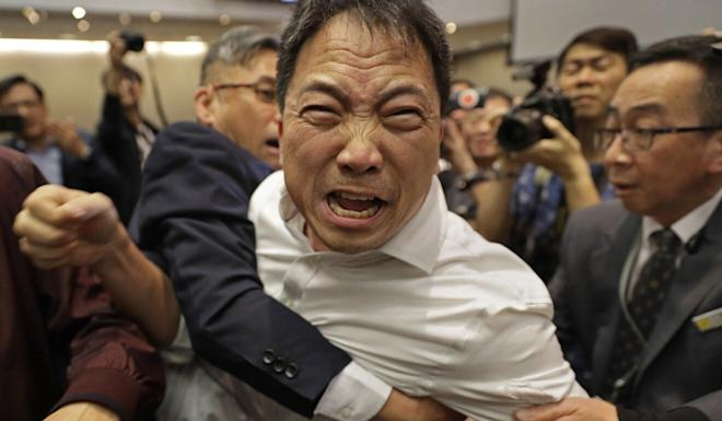 Democratic Party chairman Wu Chi-wai scuffles with Legco security guards during the extradition bill debate in May last year. Photo: AP