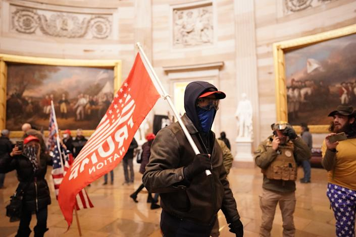 """A man dressed all in black carries a red """"Trump Nation"""" flag inside the Capitol Rotunda."""