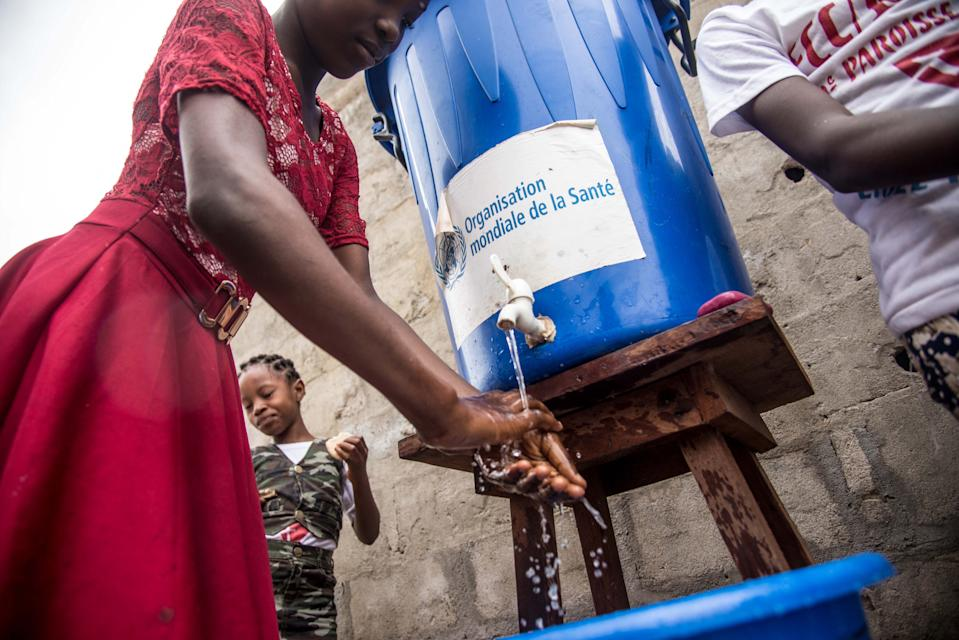 A woman washes her hands from a tank of water bearing a World Health Organization (WHO-OMS) sticker, as a prevention against Ebola virus after a Pentecost mass at the Church of Christ on May 20, 2018 in Mbandaka, northwest of DR Congo. - The Democratic Republic of Congo is preparing to launch an Ebola vaccination programme on May 21 in a bid to stop the latest outbreak of the dreaded fatal disease from spreading, as the UN's World Health Organization (WHO) put the death toll at 25. (Photo by Junior D. KANNAH / AFP) (Photo by JUNIOR D. KANNAH/AFP via Getty Images)
