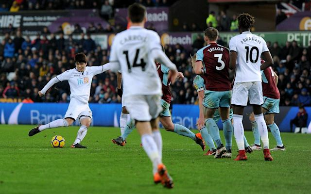 Ki Sung-Yeung struck late to clinch a crucial 1-0 triumph over Burnley to lift Swansea away from the relegation gloom. The South Korean midfielder dealt Burnley a hammer blow with eight minutes on the clock to send the Swans into 15th place and two points clear of the bottom three. Carlos Carvalhal has masterminded three victories in their last four matches, in stark contrast with Burnley, who remain in seventh spot despite their 10th match without a win. Their recent barren run looked like it was going to come to an end as Sean Dyche's men looked most likely to break the deadlock at a rain soaked Liberty Stadium. Johann Berg Gudmundson found space down the left flank and pulled the ball back for Jeff Hendrick to shoot straight into the torso of the onrushing Alfie Mawson. Sam Vokes' strength was proving troublesome for the Swansea back three and he used his body weight to full effect to shield the ball from Federico Fernandez before swivelling and shooting just wide. The home fans had to wait 37 minutes for their first chance on goal when Seung-Yung found Sam Clucas in the box, but the wet conditions were a factor as he sliced his shot high and wide. Neither side managed to get a single shot on target before Andre Marriner called time on the first period. Jordan Ayew looked to add the attacking impetus when he ran at the Burnley defence and fired the ball across the face of goal but nobody was there to convert the cross. Tom Carroll lost a midfield tussle with Cork moments later, the ball broke to Barnes, who bent the ball inches wide. The first shot on target came in the 56th minute when Gudmundsson forced Fabianksi to tip over after he unleashed a snap-shot on the half volley. Tammy Abraham was thrust into the action and almost made an instant impact when his flick-on flashed in front of Ayew, but Pope stuck out a hand to thwart the in-form frontman. But the breakthrough finally came in the 82nd minute when Kyle Naughton danced into the box and fed Ki. The South Korean took a touch and fired a shot into the bottom corner to score his first goal since May 2016, and the Swans held on for another crucial victory.