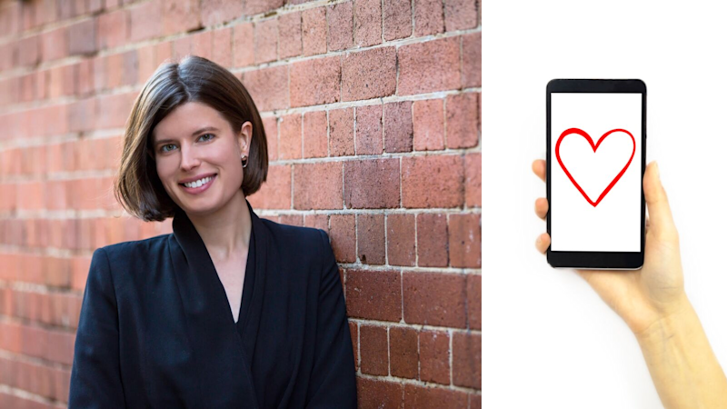 Holly Bartter is pictured against a red brick wall. She is wearing a black jacket. She has short hair, and she is smiling at the camera. On the left, a hand holds up a phone. The screen is white with a red love heart.