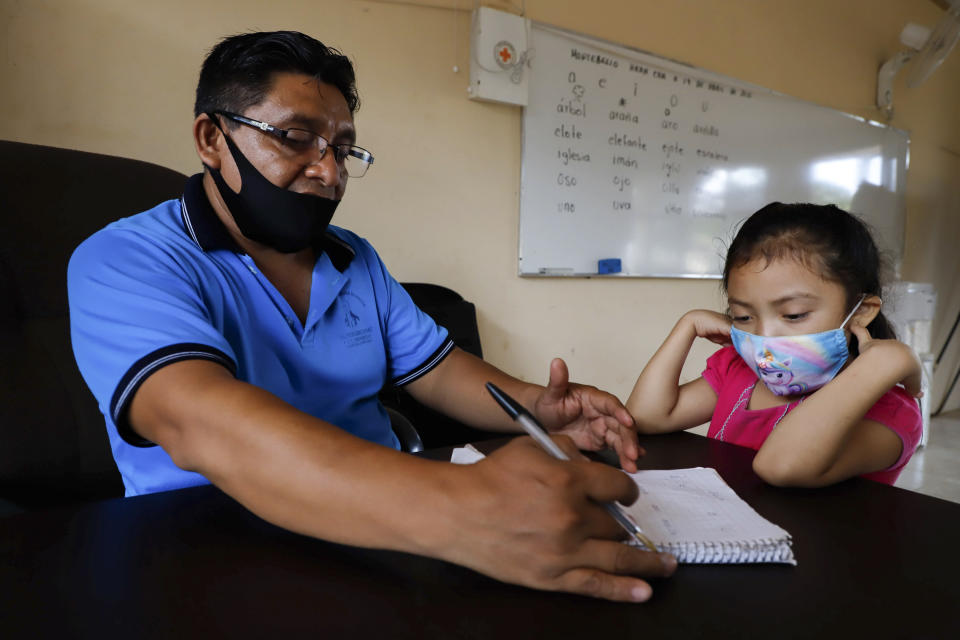 Wearing masks to curb the spread of the new coronavirus, a teacher checks the work of his 10-year-old student Jade Chan Puc during the first day of class at the Valentín Gomez Farias Indigenous Primary School in Montebello, Hecelchakan, Campeche state, Monday, April 19, 2021. Campeche is the first state to transition back to the classroom after a year of remote learning due to the pandemic. (AP Photo/Martin Zetina)
