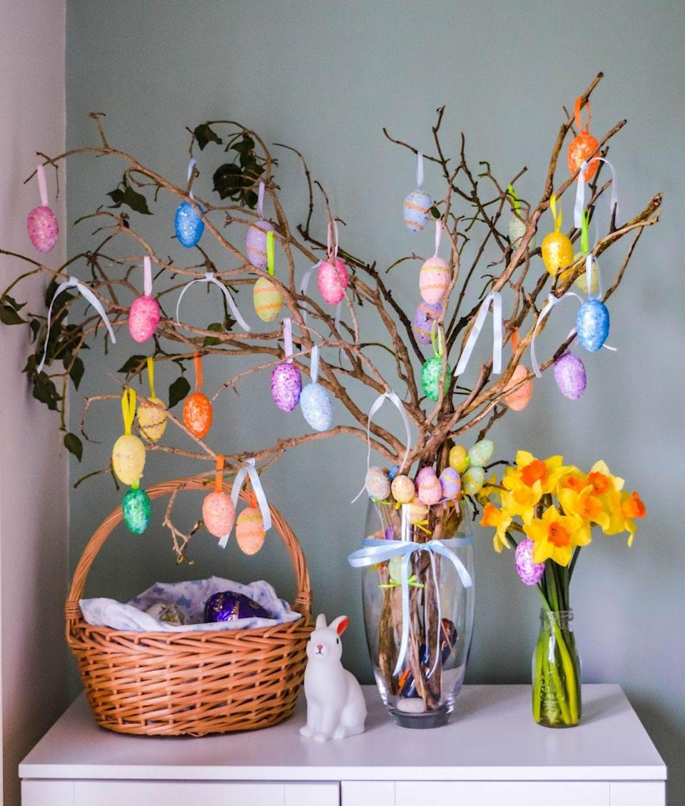 """<p>Attach coordinating ribbon to already-decorated eggs and hang from foraged branches for the cutest—and easiest— DIY ever. </p><p><strong>Get the tutorial at <a href=""""https://www.dollydowsie.com/2018/03/cheap-cheerful-diy-easter-tree.html?utm_medium=social&utm_source=pinterest&utm_campaign=tailwind_tribes&utm_content=tribes&utm_term=550901834_20259508_456546"""" rel=""""nofollow noopener"""" target=""""_blank"""" data-ylk=""""slk:Dolly Dowsie."""" class=""""link rapid-noclick-resp"""">Dolly Dowsie.</a></strong></p><p><a class=""""link rapid-noclick-resp"""" href=""""https://www.amazon.com/Joyin-Toy-Stuffers-Classroom-Supplies/dp/B01MU4ZEL1/ref=sr_1_6?tag=syn-yahoo-20&ascsubtag=%5Bartid%7C10050.g.26498744%5Bsrc%7Cyahoo-us"""" rel=""""nofollow noopener"""" target=""""_blank"""" data-ylk=""""slk:SHOP DECORATED EGGS"""">SHOP DECORATED EGGS </a></p>"""