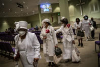 Women wearing face masks leave after a church service at the New Horizon International Church, Sunday, Oct. 4, 2020, in Jackson, Miss. Across the country, racial minorities, especially Black people, have been hit hard by COVID-19. (AP Photo/Wong Maye-E)