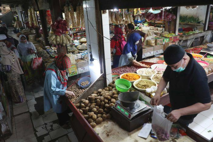 People wear face masks at a market in Jakarta.