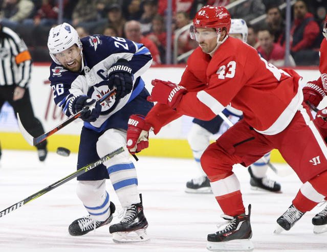 Winnipeg Jets right wing Blake Wheeler (26) shoots the puck into the corner against Detroit Red Wings center Darren Helm (43) during the first period of an NHL hockey game Friday, Oct. 26, 2018, in Detroit. (AP Photo/Duane Burleson)