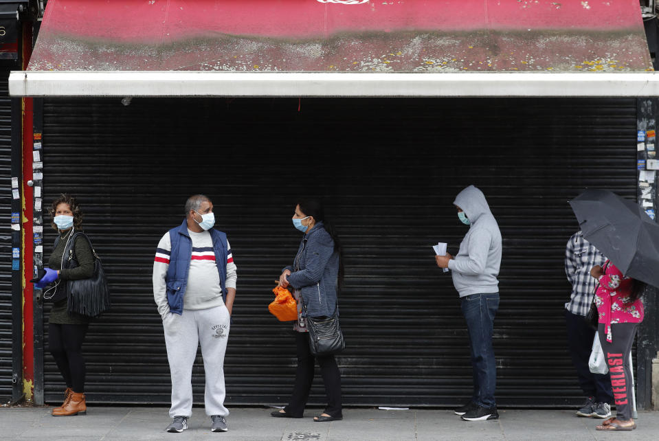 Customers queue outside a retail shop in front of a closed shop as coronavirus restrictions on non-essential retailers were lifted in London, Friday, June 19, 2020. Retailers see a much-needed boost in sales this month compared with the record lows in April as lockdown turned thriving high streets into ghost towns. (AP Photo/Frank Augstein)