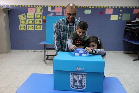 An Israeli-Arab father casts a ballot together with his children, as Israelis vote in a parliamentary election, at a polling station in Umm al-Fahm, Israel April 9, 2019. REUTERS/Ammar Awad