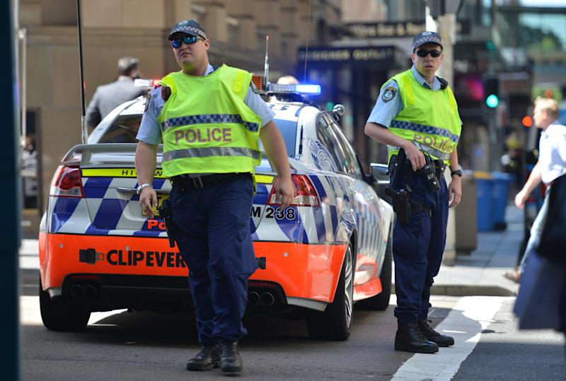 Police close a street at a cafe in Sydney on December 15, 2014 after an Iranian-born self-styled cleric took 17 people hostage (AFP Photo/Peter Parks)
