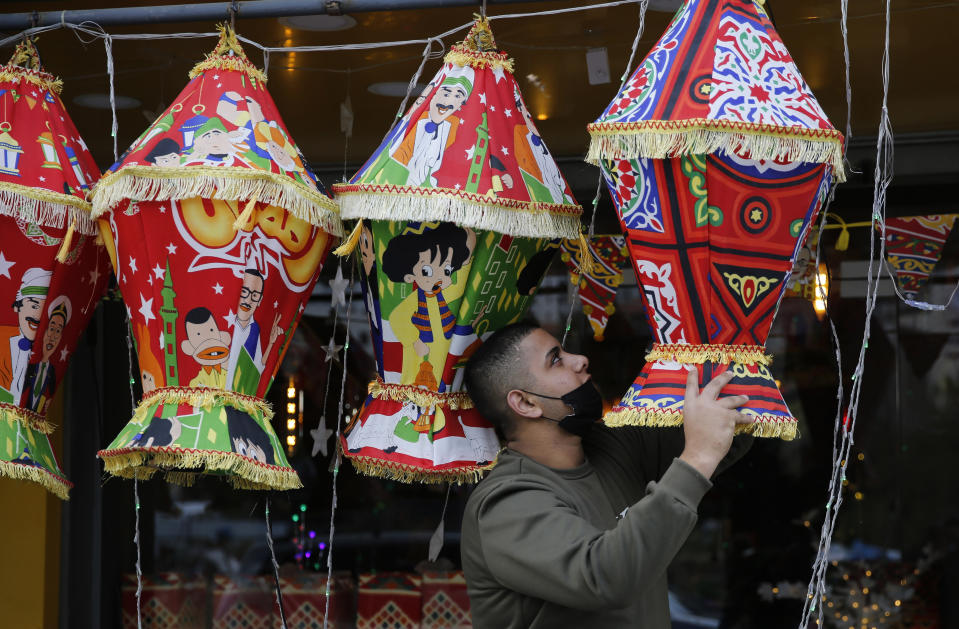 FILE - In this April 10, 2021, file photo, a Palestinian shopkeeper hangs Ramadan lanterns ahead of the Muslim fasting month of Ramadan, in the West Bank city of Nablus. Muslims are facing their second Ramadan in the shadow of the pandemic. Many Muslim majority countries have been hit by an intense new coronavirus wave. While some countries imposed new Ramadan restrictions, concern is high that the month's rituals could stoke a further surge. (AP Photo/Majdi Mohammed, File)