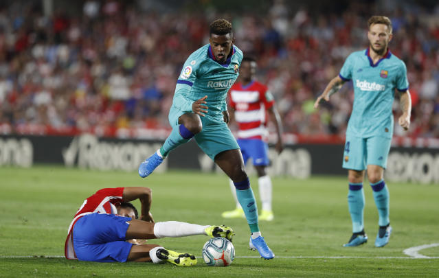 Barcelona's Nelson Semedo, top, and Granada's Angel Montoro fight for the ball during the Spanish La Liga soccer match between Barcelona and Granada at the Los Carmenes stadium in Granada, Spain, Saturday, Sept. 21, 2019. (AP Photo/Miguel Morenatti)
