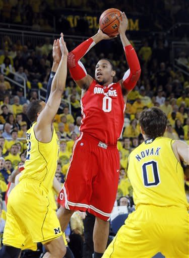 Ohio State forward Jared Sullinger (0) shoots over Michigan forward Jordan Morgan, left, and guard Zack Novak (0) in the first half of an NCAA college basketball game, Saturday, Feb. 18, 2012, in Ann Arbor, Mich. (AP Photo/Tony Ding)