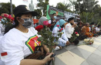 Interfaith activists hold flowers during a prayer for the crew of Indonesian Navy submarine KRI Nanggala that sank in Bali Sea, in Surabaya, East Java, Indonesia, Sunday, April 25, 2021. Indonesia's military on Sunday officially admitted there was no hope of finding survivors from the submarine that sank and broke apart last week with 53 crew members aboard, and that search teams had located the vessel's wreckage on the ocean floor. (AP Photo/Trisnadi)