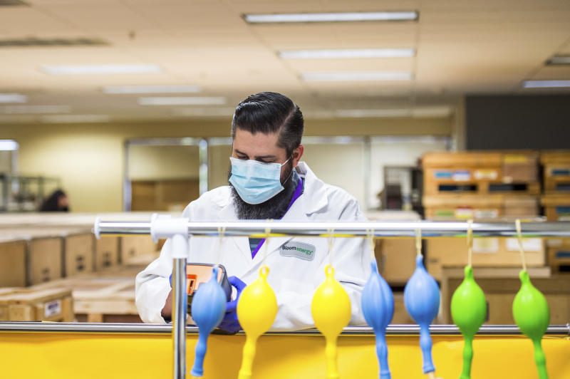 A staff member works at the ventilator lung testing station at Bloom Energy in Sunnyvale, Calif. Saturday, March 28, 2020. Bloom Energy is a fuel cell generator company that has switched over to refurbishing ventilators as an increasing number of patients experience respiratory issues as a result of COVID-19. (Beth LaBerge/Pool Photo via AP)