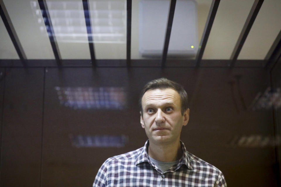 FILE - In this Saturday, Feb. 20, 2021 file photo, Russian opposition leader Alexei Navalny stands in a cage in the Babuskinsky District Court in Moscow, Russia. Alexei Navalny's lawyer Mikhailova said Navalny was taken to a hospital outside prison on Wednesday, March 24 for magnetic resonance tomography but wasn't given the results. She said Navalny has received pills and ointment for his pain, but prison authorities refused to accept medicines that lawyers brought to him. (AP Photo/Alexander Zemlianichenko, File)