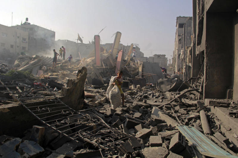 FILE - In this Aug. 2, 2014 file photo, Palestinians search through rubble of homes destroyed in Israeli strikes in Rafah, southern Gaza Strip. The Israeli military said on Wednesday Aug. 15, 2018, its investigation focused on an Aug. 1, 2014, battle in the southern Gaza town of Rafah, one of the bloodiest incidents of the 2014 war in the Gaza Strip, has found no criminal wrongdoing by Israeli forces, although human rights advocates accused the military of a whitewash. (AP Photo/Hatem Ali, FILE)