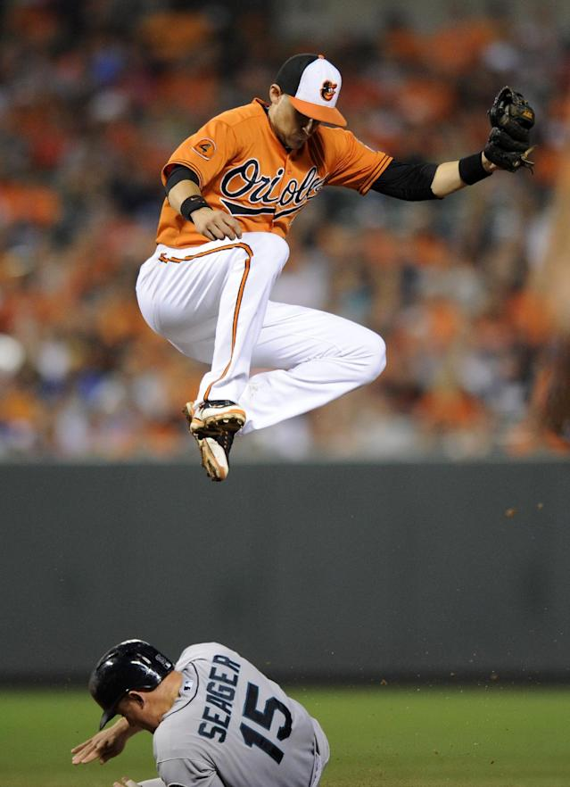 Seattle Mariners' Kyle Seager (15) steals second against Baltimore Orioles shortstop Ryan Flaherty, top, during the fifth inning of a baseball game, Saturday, Aug. 3, 2013, in Baltimore. (AP Photo/Nick Wass)