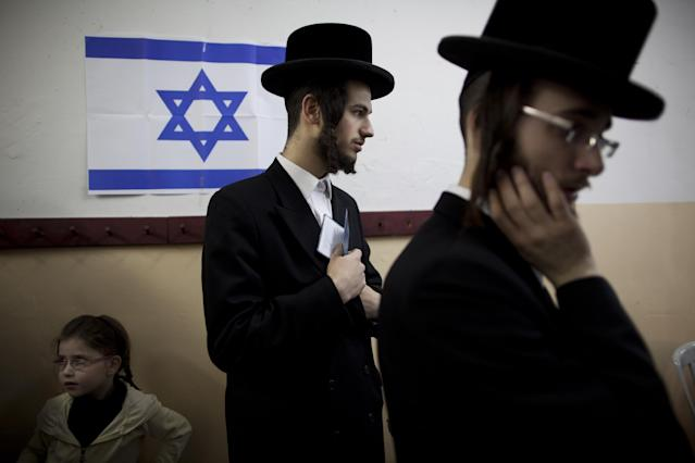 An Ultra-orthodox Jewish man holds his ID card as he waitS to vote in Bnei Brak, Israel, during legislative elections, Tuesday, Jan. 22, 2013. Israelis began trickling into polling stations Tuesday morning to cast their votes in a parliamentary election expected to return Prime Minister Benjamin Netanyahu to office despite years of stalled peacemaking with the Palestinians and mounting economic troubles. Polls indicate about a dozen of 32 parties competing in Tuesday's election have a chance of winning seats in the 120-member parliament. Most parties fall either into the right-wing-religious or center-left camp, and surveys indicate hard-line and ultra-Orthodox Jewish parties will command a majority. (AP Photo/Oded Balilty)