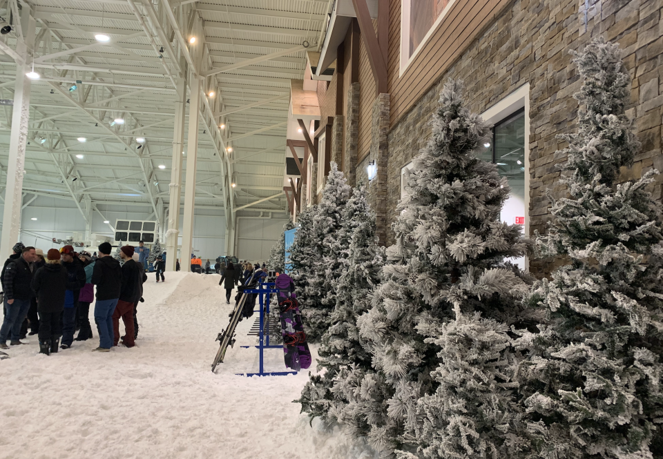 To make Big SNOW look less like a stark warehouse and more like a mountain resort, designers were inspired to replicate a ski chalet and pine trees were added to enhance the landscape. (Photo credit: Kristen Despotakis/Yahoo Finance)