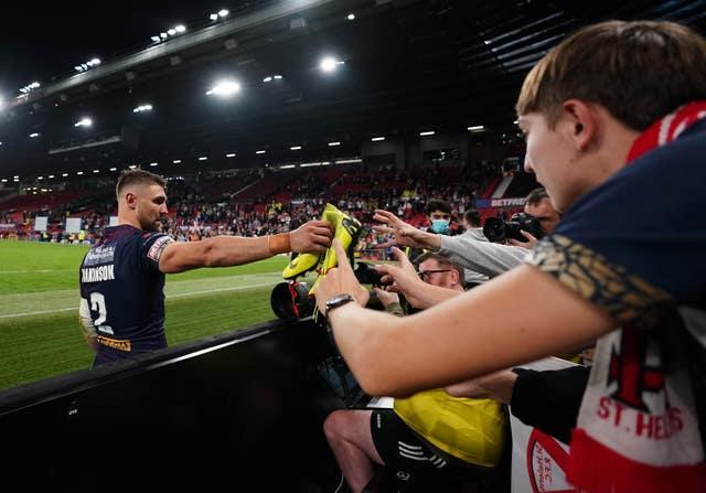 St Helens' Tommy Makinson gives his boots to a fan
