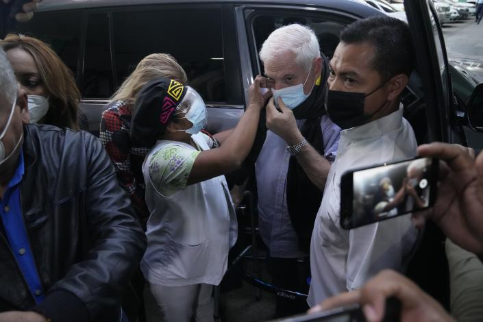 Panama's former President Ricardo Martinelli gets help adjusting his mask from an unidentified person as he arrives to court for the start of his trial in Panama City, Wednesday, July 21, 2021. Martinelli faces trial for alleged eavesdropping on political rivals and journalists during his administration, the same case for which he was acquitted in 2018. (AP Photo/Arnulfo Franco)