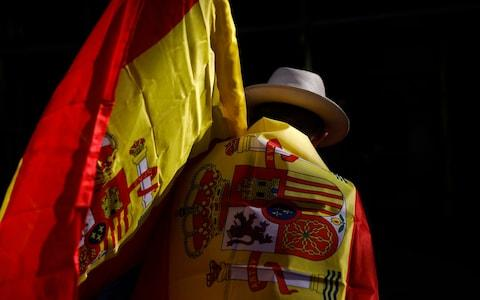 A man wearing a Spanish flag walks along a street ahead of a rally in Barcelona - Credit: AP Photo/Santi Palacios