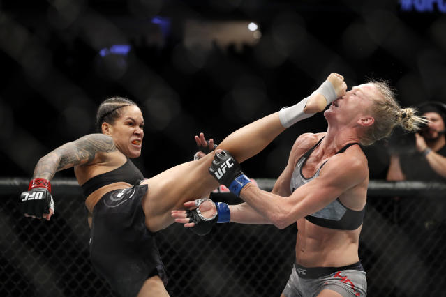 Amanda Nunes lands a kick on Holly Holm that knocked her to the mat in the first round of their bantamweight title bout at UFC 239 in Las Vegas. (AP)