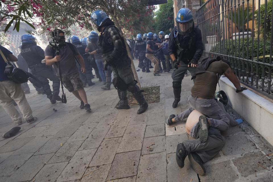 EDS NOTE NUDITY: A demonstrator is blocked by a police officer during clashes broke out between demonstrators and Italian Policemen in riot gears on the occasion of a protest against the G20 Economy and Finance ministers and Central bank governors' meeting in Venice, Italy, Saturday, July 10, 2021. (AP Photo/Luca Bruno)