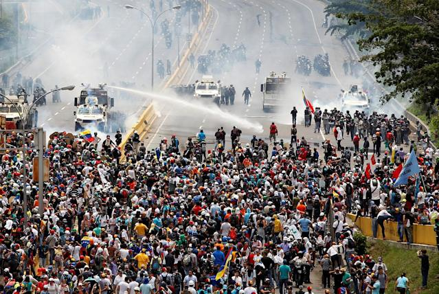 <p>Opposition supporters clash with riot police during a rally against President Nicolas Maduro in Caracas, Venezuela, May 3, 2017. (Christian Veron/Reuters) </p>