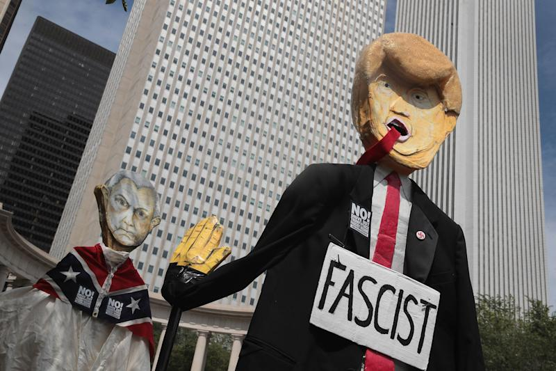 Demonstrators in Chicago protesting the alt-right and mourning Charlottesville, Virginia, victims carry puppets of President Donald Trump and U.S. Attorney General Jeff Sessions on Aug. 13.