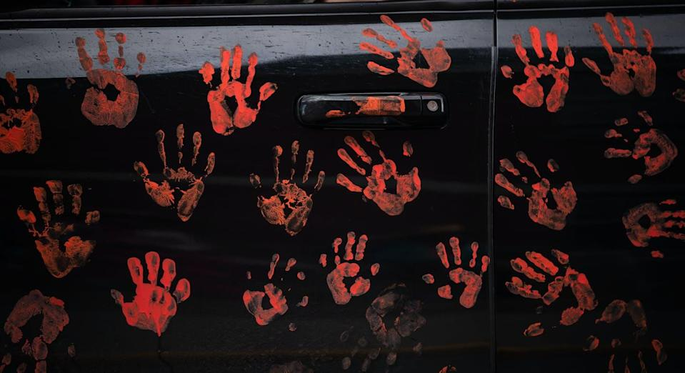 """<span class=""""caption"""">Handprints are seen on the side of a truck riding in a convoy of truckers and other vehicles in support of the Tk'emlups te Secwepemc people after the remains of 215 children were discovered buried near the former Kamloops Indian Residential School, in Kamloops, B.C.. </span> <span class=""""attribution""""><span class=""""source""""> THE CANADIAN PRESS/Darryl Dyck</span></span>"""