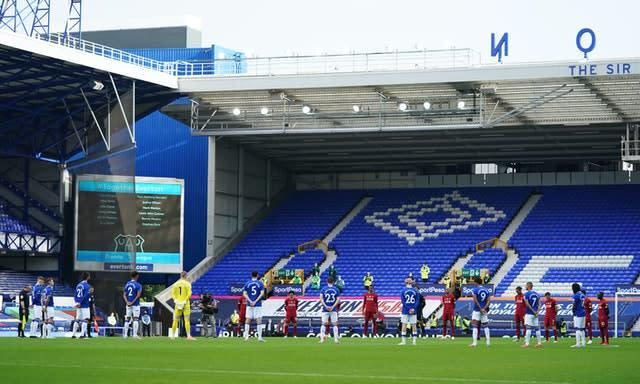 Players and officials observe a minute's silence in memory of the victims of the coronavirus before the Merseyside derby (Jon Super/NMC Pool)
