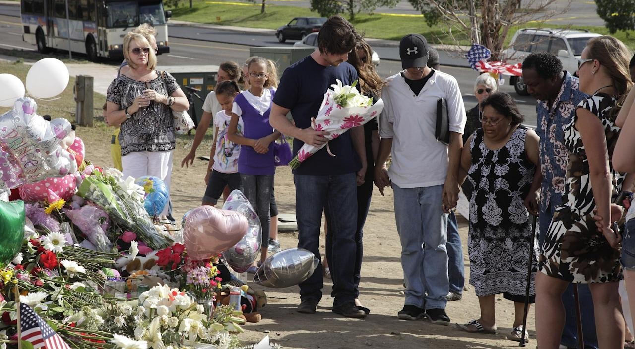 """Actor Christian Bale, holding flowers at center, joins hands and prays with visitors to a memorial to the victims of Friday's mass shooting, Tuesday, July 24, 2012, in Aurora, Colo. Twelve people were killed when a gunman opened fire during a late-night showing of the movie """"The Dark Knight Rises,"""" which stars Bale as Batman. (AP Photo/Ted S. Warren)"""