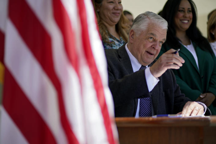 Nevada Democratic Gov. Steve Sisolak signs a bill into law Friday, June 11, 2021, in Las Vegas. The law would make Nevada the first to vote on the 2024 presidential primary contests, though national political parties would need to agree to changes in the calendar or state parties could risk losing their delegates at presidential nominating conventions. (AP Photo/John Locher)