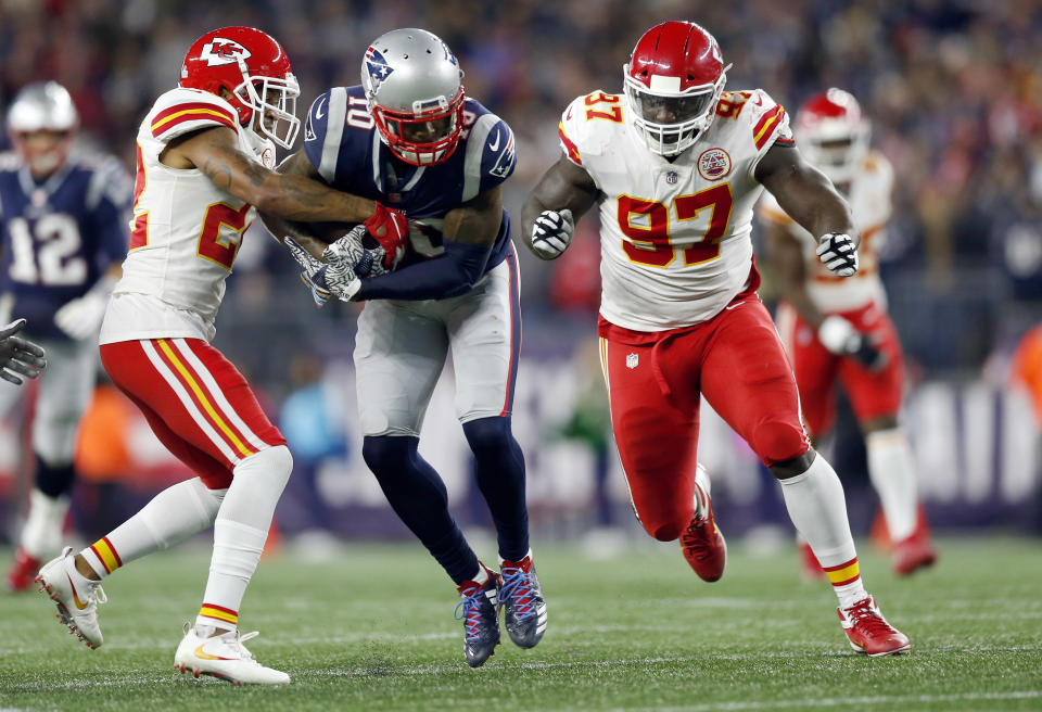 New England Patriots wide receiver Josh Gordon, center, runs after catching a pass, as Kansas City Chiefs defensive back Orlando Scandrick (22) and defensive end Allen Bailey (97) defend during the first half of an NFL football game, Sunday, Oct. 14, 2018, in Foxborough, Mass. (AP Photo/Michael Dwyer)
