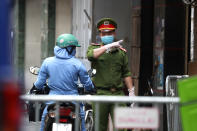 A police officer talks to a woman at the barricaded entrance of an alley where one of its residents has COVID-19 in Hanoi, Vietnam on Wednesday, July 29, 2020. Vietnam intensifies protective measures as the number of locally transmissions, starting at a hospital in the popular beach city of Da Nang, keeps increasing since the weekend. (AP Photo/Hau Dinh)